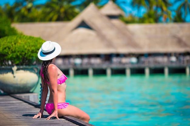 Mooie vrouw zittend op een houten steiger in tropische resort