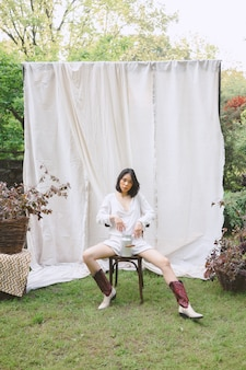 Mooie vrouw zittend op een stoel in de tuin.