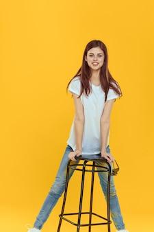 Mooie vrouw zittend op een stoel modieuze kleding levensstijl gele achtergrond
