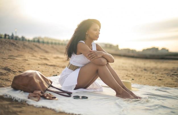 Mooie vrouw zittend op het strand, gekleed in een witte jurk
