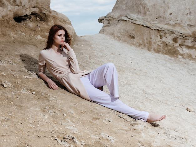 Mooie vrouw zittend op het zand elegante stijl