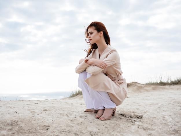 Mooie vrouw zittend op het zand model reizen