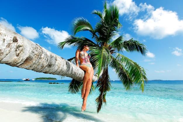 Mooie vrouw zittend op palm op zee