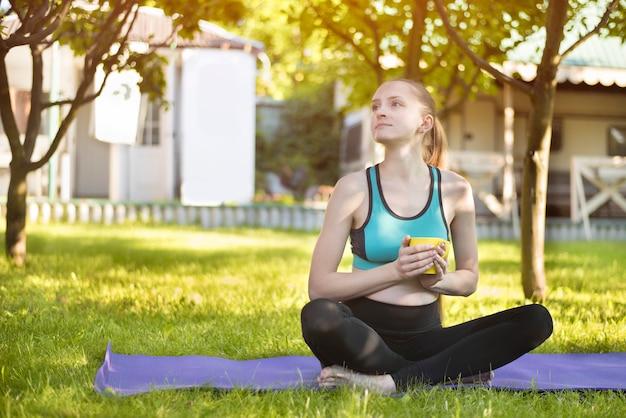 Mooie vrouw zittend op yoga mat met kopje thee