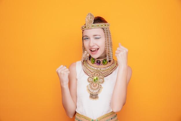 Mooie vrouw zoals cleopatra in oud egyptisch kostuum, blij en opgewonden, balde vuisten die zich verheugen over haar succes op sinaasappel