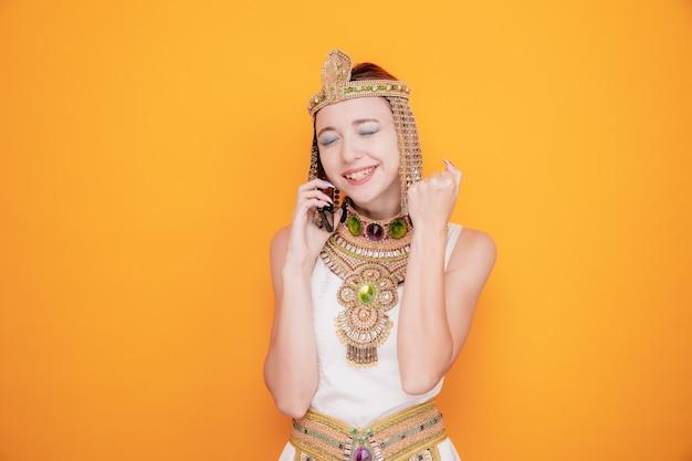 Mooie vrouw zoals cleopatra in oud egyptisch kostuum blij en opgewonden die vuist opheft terwijl ze op mobiele telefoon op oranje praat
