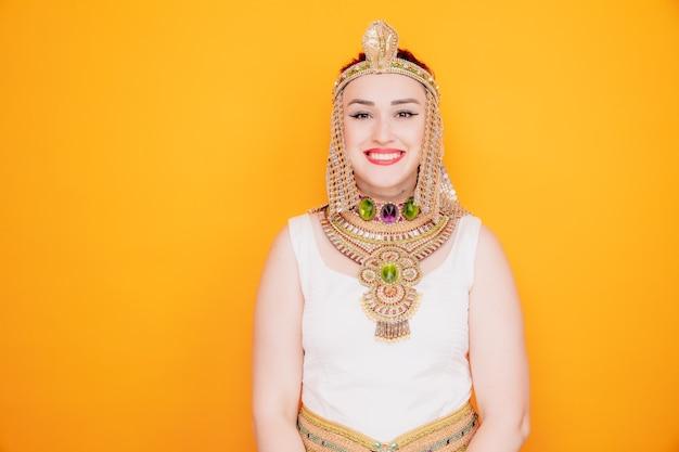 Mooie vrouw zoals cleopatra in oud egyptisch kostuum, blij en positief glimlachend vrolijk op sinaasappel