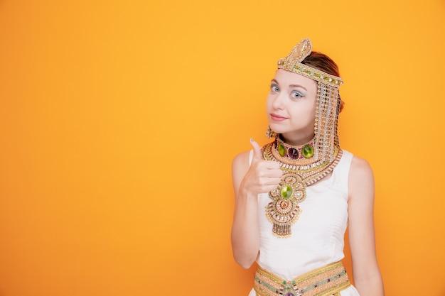 Mooie vrouw zoals cleopatra in oud egyptisch kostuum, blij en positief glimlachend zelfverzekerd met duim omhoog op sinaasappel