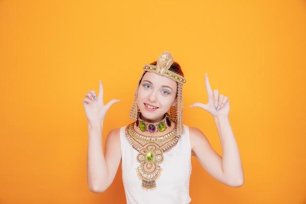 Mooie vrouw zoals cleopatra in oud egyptisch kostuum, blij en positief met wijsvingers op sinaasappel