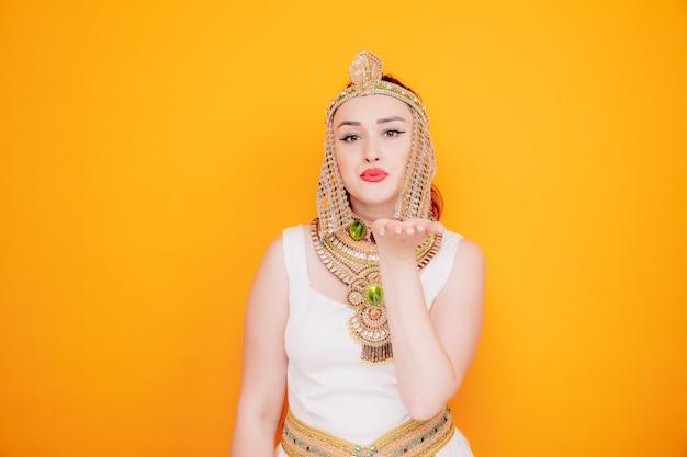 Mooie vrouw zoals cleopatra in oud egyptisch kostuum, blij en positief verzendende luchtkus op sinaasappel