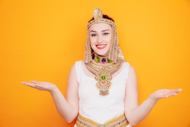 Mooie vrouw zoals cleopatra in oud egyptisch kostuum, blij en verheugd glimlachend breed uitspreidende armen naar de zijkanten op oranje