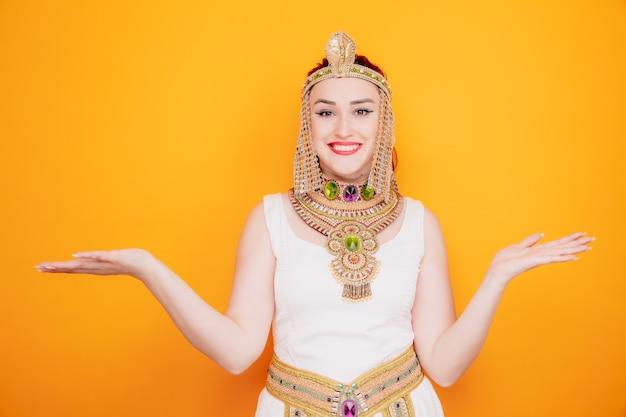 Mooie vrouw zoals cleopatra in oud egyptisch kostuum, blij en vrolijk glimlachend, breed uitspreidende armen naar de zijkanten op oranje
