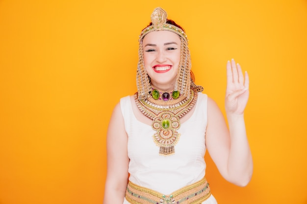 Mooie vrouw zoals cleopatra in oud egyptisch kostuum, blij en vrolijk lachend met nummer vier met vingers op sinaasappel
