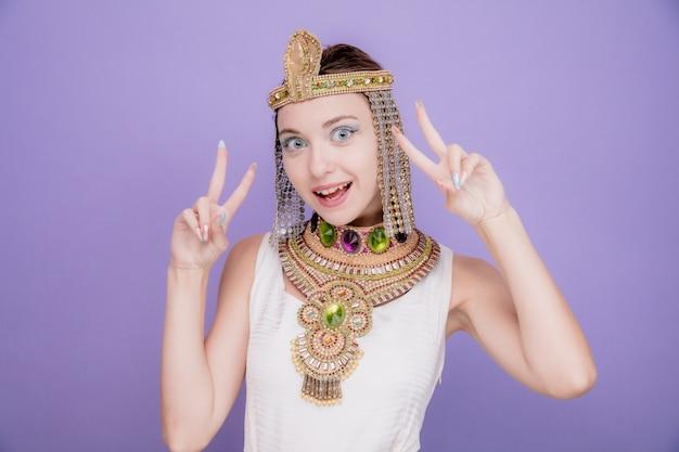 Mooie vrouw zoals cleopatra in oud egyptisch kostuum, blij en vrolijk met v-tekens die vrolijk op paars glimlachen