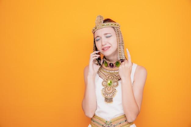 Mooie vrouw zoals cleopatra in oud egyptisch kostuum die gefrustreerd kijkt terwijl ze op mobiele telefoon praat en arm opheft met teleurgestelde uitdrukking op oranje