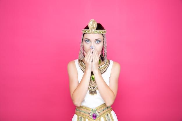 Mooie vrouw zoals cleopatra in oud egyptisch kostuum die geschokt is over mond met handen op roze