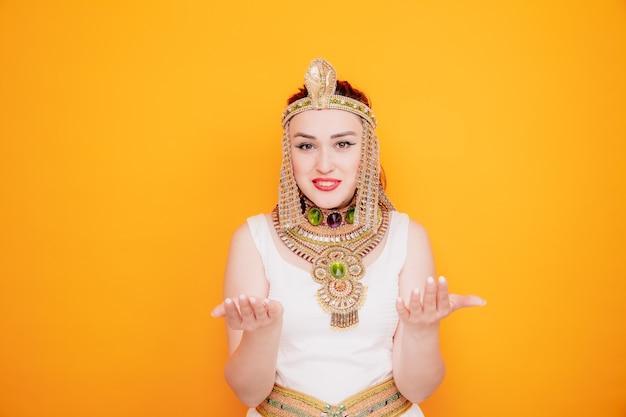 Mooie vrouw zoals cleopatra in oud egyptisch kostuum die handen in ongenoegen op oranje steekt