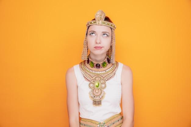 Mooie vrouw zoals cleopatra in oud egyptisch kostuum die opkijkt om ongelukkig en ontevreden te zijn en een wrange mond op sinaasappel te maken