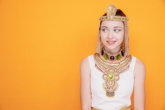 Mooie vrouw zoals cleopatra in oud egyptisch kostuum die opzij kijkt glimlachend sluw op sinaasappel