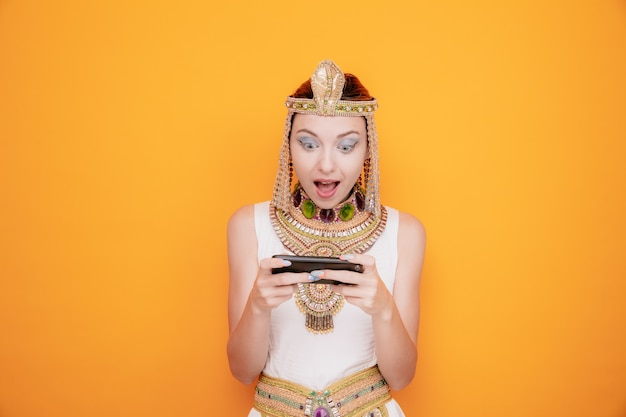 Mooie vrouw zoals cleopatra in oud egyptisch kostuum die spelletjes speelt met smartphone blij en opgewonden op sinaasappel