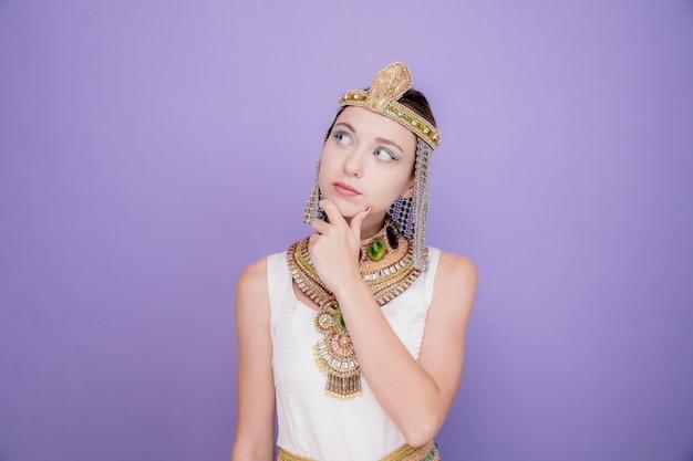 Mooie vrouw zoals cleopatra in oud egyptisch kostuum die verbaasd opkijkt met de hand op haar kin op paars