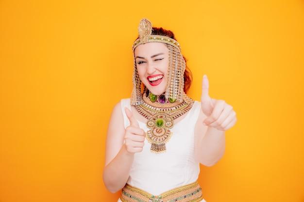 Mooie vrouw zoals cleopatra in oud egyptisch kostuum gelukkig en positief glimlachend vrolijk knipogend duimen omhoog op oranje