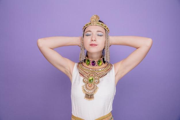 Mooie vrouw zoals cleopatra in oud egyptisch kostuum gelukkig en positief met handen achter haar hoofd met ogen gesloten op paars