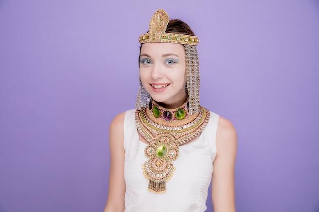 Mooie vrouw zoals cleopatra in oud egyptisch kostuum gelukkig en vrolijk glimlachend breed op paars