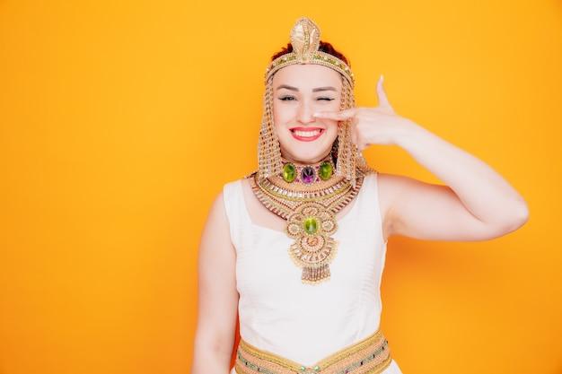Mooie vrouw zoals cleopatra in oud egyptisch kostuum gelukkig en vrolijk wijzend met wijsvinger naar haar neus glimlachend op oranje