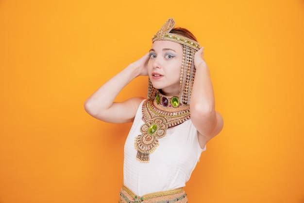 Mooie vrouw zoals cleopatra in oud egyptisch kostuum gelukkig en zelfverzekerd glimlachend op sinaasappel
