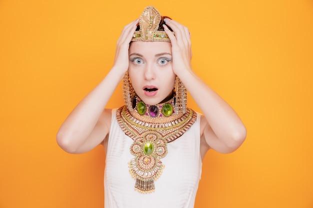 Mooie vrouw zoals cleopatra in oud egyptisch kostuum maakte zich zorgen om haar hoofd vast te houden in paniek op oranje