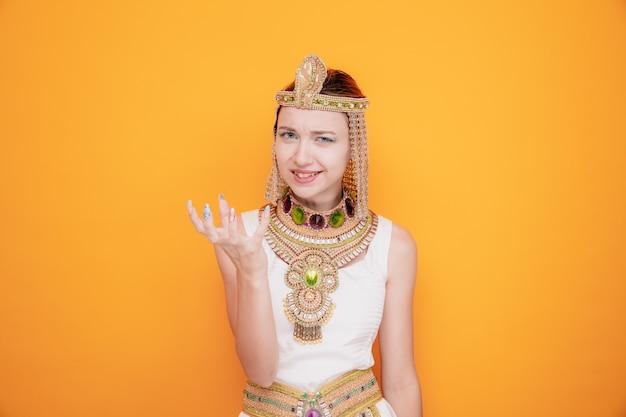 Mooie vrouw zoals cleopatra in oud egyptisch kostuum met boos gezicht dat arm opheft in ongenoegen met agressieve uitdrukking op oranje