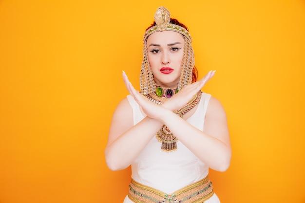 Mooie vrouw zoals cleopatra in oud egyptisch kostuum met een serieus gezicht dat een stopgebaar maakt dat de armen kruist op sinaasappel