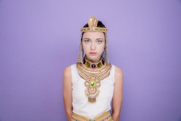 Mooie vrouw zoals cleopatra in oud egyptisch kostuum met serieuze zelfverzekerde uitdrukking op paars