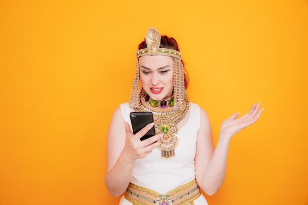 Mooie vrouw zoals cleopatra in oud egyptisch kostuum met smartphone die arm opheft met teleurgestelde uitdrukking boos en gefrustreerd op oranje