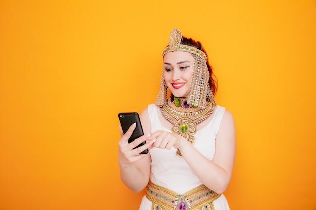 Mooie vrouw zoals cleopatra in oud egyptisch kostuum met smartphone die een bericht typt, gelukkig en positief glimlachend vrolijk op oranje