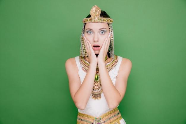 Mooie vrouw zoals cleopatra in oud egyptisch kostuum verbaasd en verrast op groen