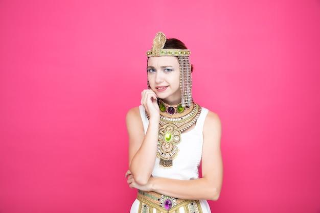 Mooie vrouw zoals cleopatra in oud egyptisch kostuum verward en bezorgd over roze