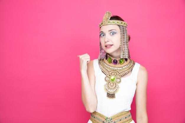 Mooie vrouw zoals cleopatra in oud egyptisch kostuum verward en bezorgd wijzend terug met duim op roze