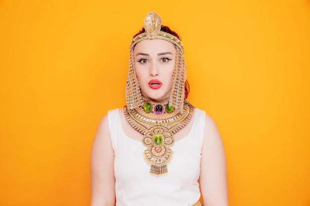 Mooie vrouw zoals cleopatra in oud egyptisch kostuum verward en verrast op sinaasappel