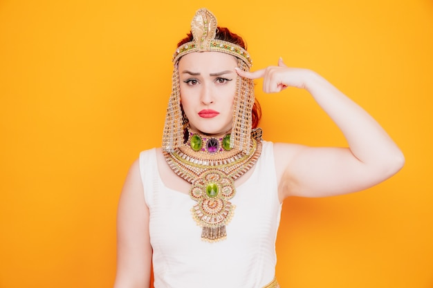 Mooie vrouw zoals cleopatra in oud egyptisch kostuum verward wijzend met wijsvinger naar haar tempel verward op oranje