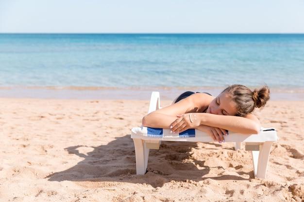 Mooie vrouw zonnebaadt op de zonnebank op het strand en heeft een lachend gezicht gemaakt van sunblock op haar hand.