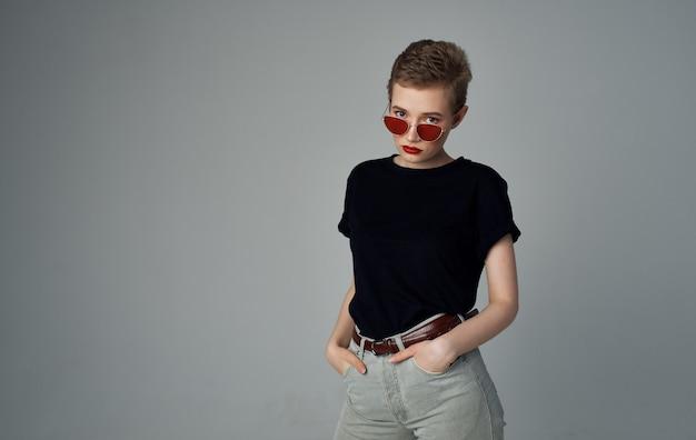 Mooie vrouw zonnebril modieuze kleding elegante stijl kort kapsel