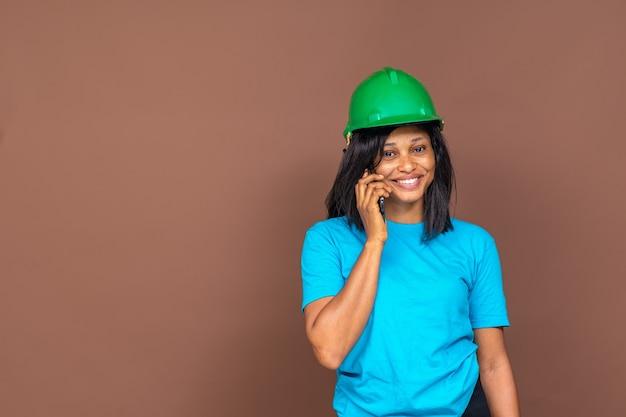 Mooie vrouwelijke aannemer die lacht terwijl hij telefoneert, staande voor een effen achtergrond