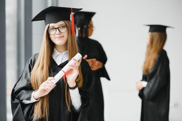 Mooie vrouwelijke afgestudeerde die uit een groep studenten duidelijk uitkomt