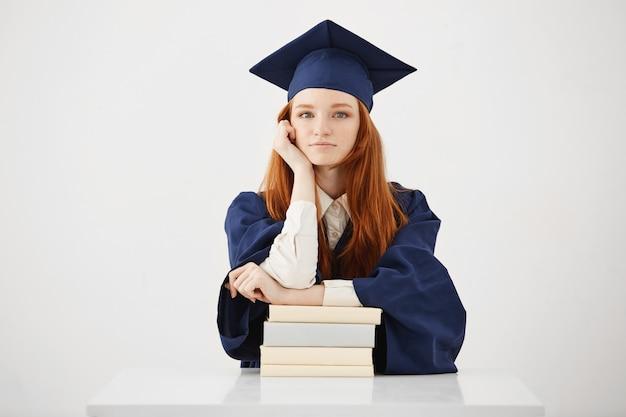 Mooie vrouwelijke afgestudeerde zitten met boeken glimlachen.