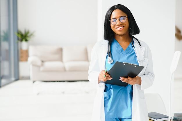 Mooie vrouwelijke afro-amerikaanse medische verpleegster met een stethoscoop