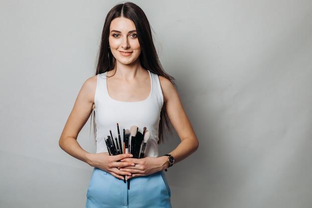 Mooie vrouwelijke artiest met make-upborstels in de schoonheidssalon. op een lichte muur