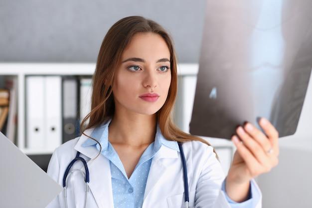 Mooie vrouwelijke arts in arm houden en kijken