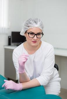 Mooie vrouwelijke arts in glazen en een wit uniform zit op een stoel in roze wegwerphandschoenen en een pet in het kantoor van de kliniek